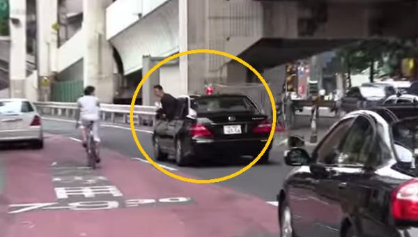 Nhân viên đoàn hộ tống Thủ tướng Nhật Bản cúi đầu cảm ơn người dân đã nhường đường