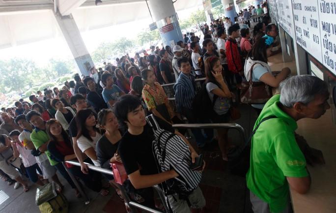 Dòng người xếp hàng mua vé xe để rời thủ đô tại một trạm xe buýt ở Bangkok, 27/10/2011.
