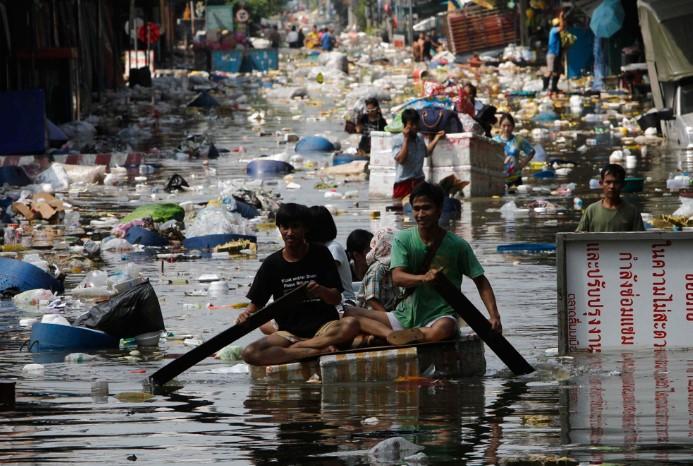 Người dân mang theo đồ đạc cá nhân bơi qua dòng nước lũ ô nhiễm sơ tán khỏi một khu chợ bị ngập ở Bangkok, 24/10/2011.