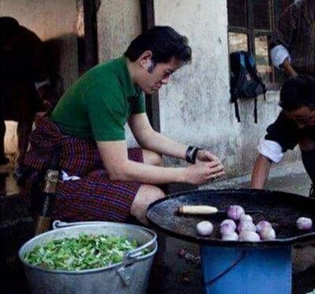 Quốc vương này tự tay vào bếp, xắt hành và ớt để chuẩn bị bữa ăn cho học sinh tại trường học cộng đồng.