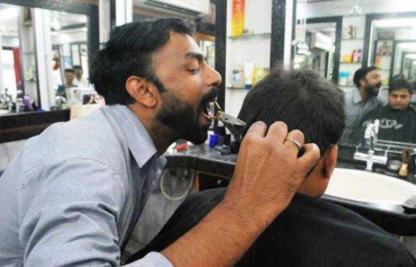 Ansar Ahmad với màn cắt tóc bằng miệng. (Ảnh: Internet)