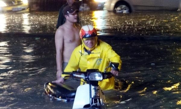 Người thanh niên không mặc áo là người dân sống trên đường Nguyễn Hữu Cảnh, Q. Bình Thạnh. Anh không ngại dòng nước bẩn, lội ra đường giúp nhiều người đi xe máy gặp sự cố.
