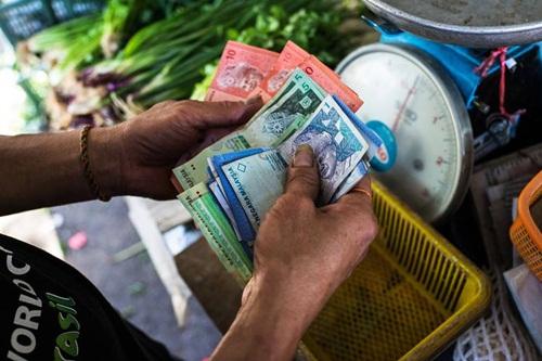 Một người bán hàng đang đếm tiền tại một khu chợ ở Malaysia. Ảnh: Bloomberg