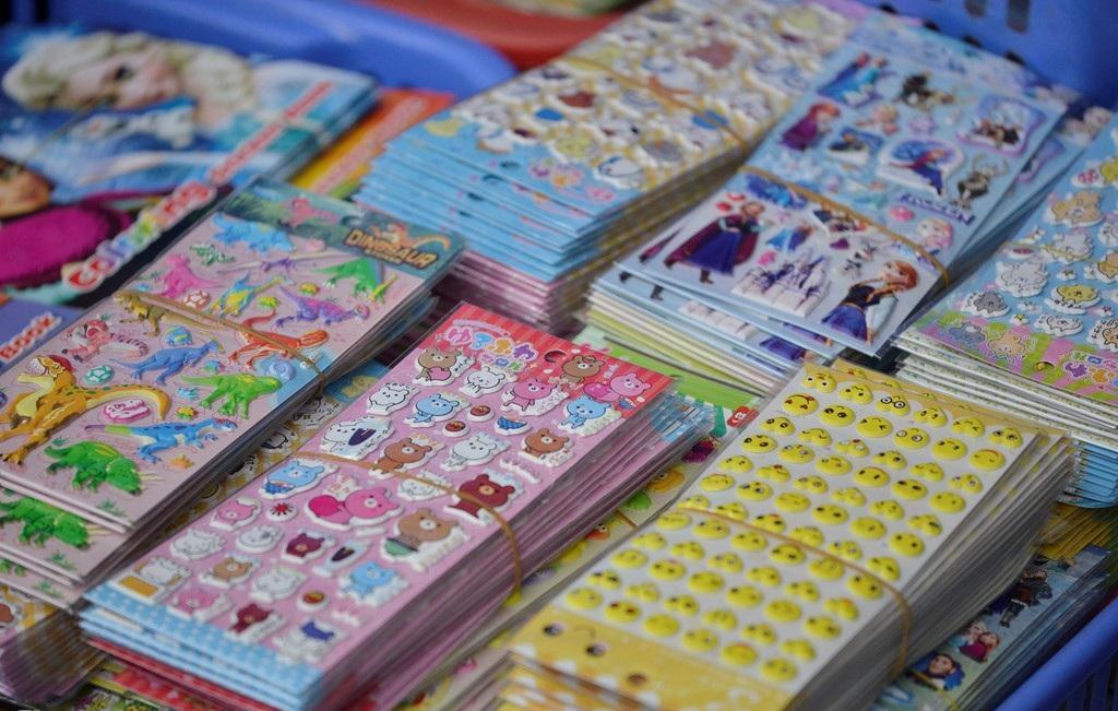 Những miếng dán hoạt hình có nguồn gốc từ Trung Quốc được bày bán nhiều tại Hàng Mã. Cách đây không lâu các cơ quan chức năng khuyến cáo không nên dùng đồ chơi này, vì chất Phthalate có trong miếng dán hoạt hình là chất độc hại có khả năng gây ung thư và vô sinh cho trẻ em. Trước đó, chất này từng được phát hiện trong sản phẩm thú nhún Trung Quốc bày bán tại Việt Nam. (Ảnh: Internet)