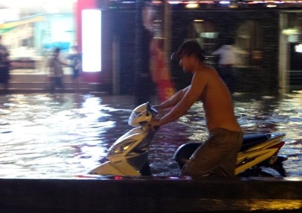 """Nam thanh niên này làm việc ở một vựa ve chai trên đường Nguyễn Hữu Cảnh. Anh cũng là """"soái ca"""" của nhiều người đang bị cô lập giữa dòng nước bẩn."""