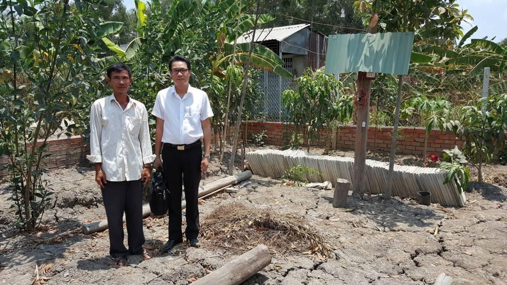 Ông Bỉ (trái) bên mảnh đất đã tháo dỡ cái chòi vịt.