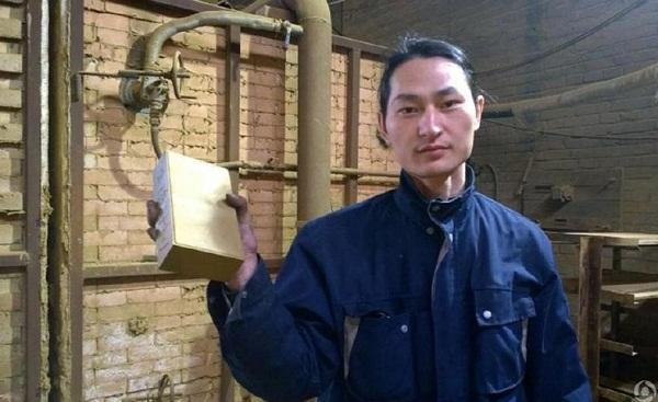 Người nghệ sĩ vớiviên gạch được làm từ bụi Bắc Kinh.