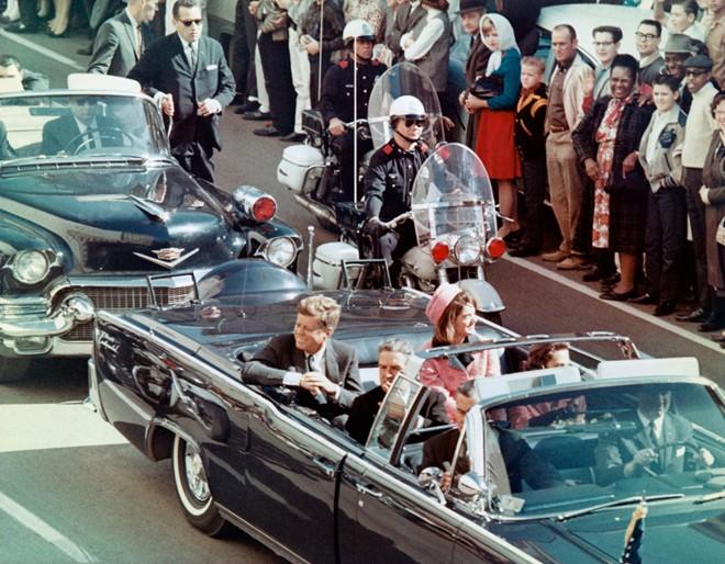 Tổng thống Kennedy và phu nhân cười tươi với người dân đứng xung quanh đường chào đón họ ở Dallas, Texas, chỉ vài phút trước khi bị ám sát.