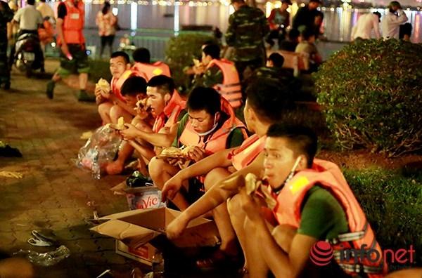 Việc thu gom cá chết được thực hiện liên tục không ngừng nghỉ. (Trong ảnh: Lực lượng thu gom cá Hồ Tây phải tranh thủ nghỉ ngơi và ăn giữa đêm khuya).