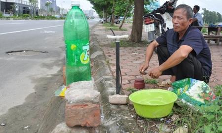 Chú Định với công việc sửa, vá xe đạp xe máy trên đường Lê Văn Lương kéo dài.