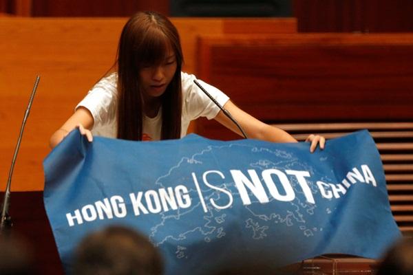 """Tân nghị sĩ Yau Wai-ching trưng tấm banner ghi """"Hong Kong không phải là Trung Quốc"""" trước khi tuyên thệ tại ngày 12/10 - Ảnh: Reuters"""