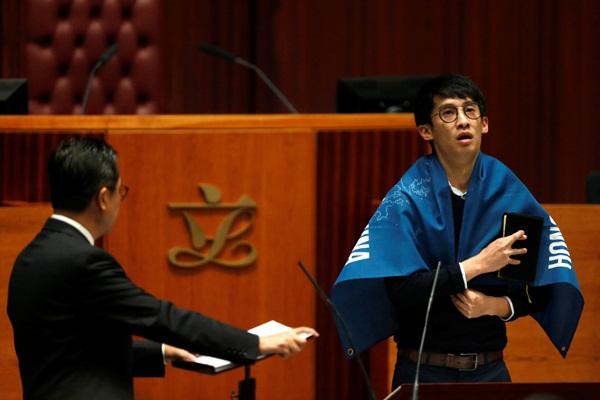 Tân nghị sĩ Baggio Leung khoác lên mình tấm banner phản đối Trung Quốc - Ảnh: Reuters