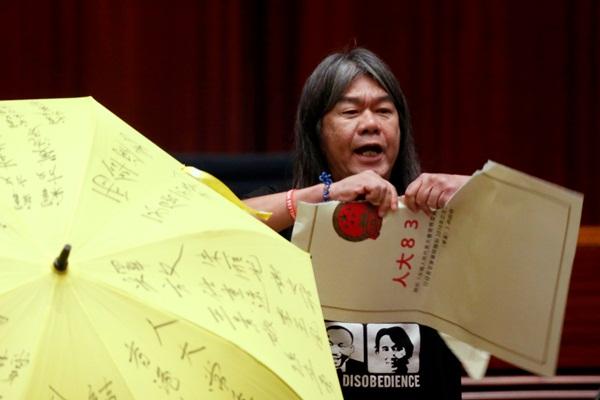 """Nghị sị Leung Kwok-hung xé một bản mô phỏng đề xuất luật """"chống lật độ"""" tại buổi tuyên thệ - Ảnh: Reuters"""
