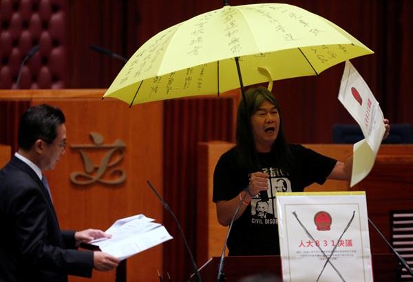 Nghị sị Leung Kwok-hung còn cầm cả một chiếc dù, biểu tượng phong trào ủng hộ dân chủ của Hong Kong, tại buổi tuyên thệ - Ảnh: Reuters