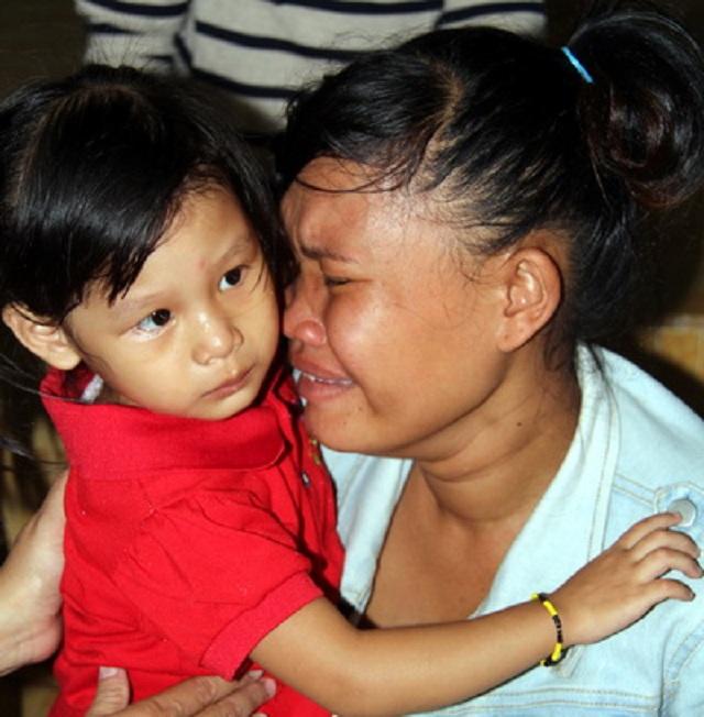 Chị Liên bật khóc ôm đứa con 3 năm nay mình nuôi dưỡng trước khi trao trả lại cho vợ chồng anh Khiên. (Ảnh: Phước Tuấn)