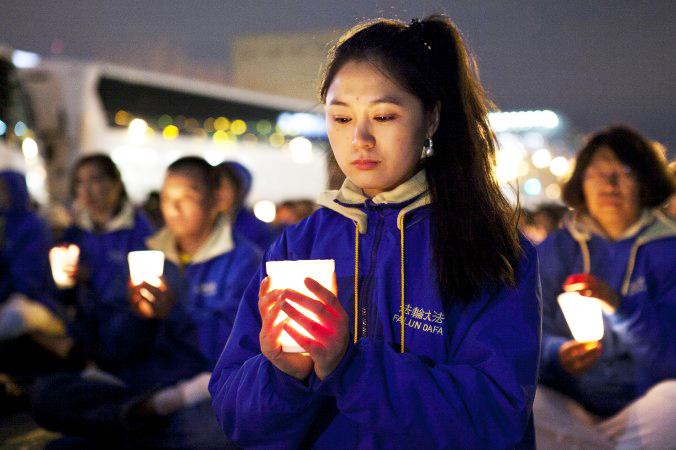 Hình ảnh các học viên Pháp Luân Công thắp nến tượng niệm những người vô tội bị bức hại tại Trung Quốc. (Ảnh: Internet)