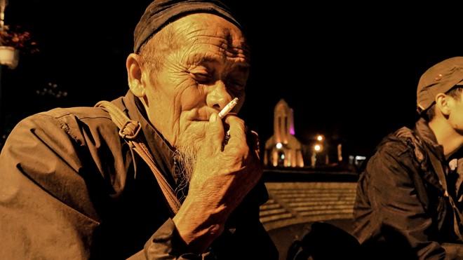 Được khách du lịch tặng bao thuốc lá, ông Páo vui vẻ hút. (Ảnh: Hoàng Như)