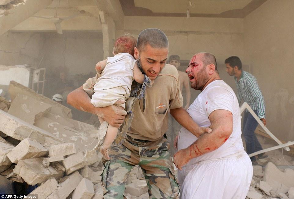 Một người đàn ông Syria bế em bé tới nơi an toàn.
