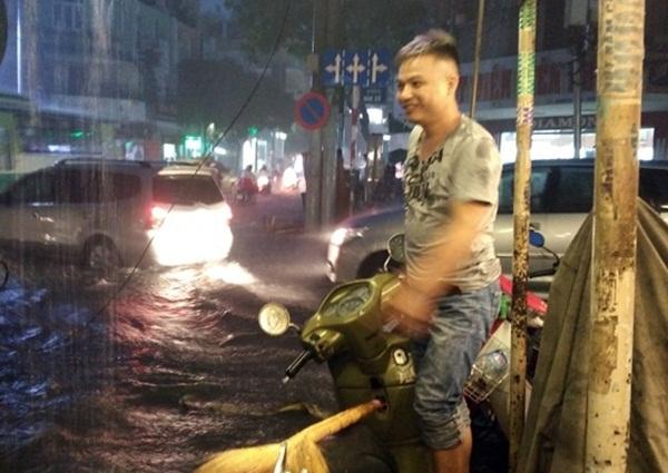 """Anh chàng này ngụ trên đường Điện Biên Phủ. Anh không ngại trời mưa, nước bẩn để đứng làm """"biển báo"""" trước miệng hố sâu do thi công vỉa hè để cảnh báo người dân tránh xa khu vực này."""