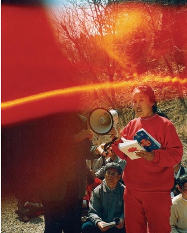 """Bức ảnh có chòm sáng hình vòng cung màu đỏ vàng này chụp khi mọi người cùng đọc cuốn sách """"Chuyển Pháp Luân"""". (Ảnh: Internet)"""