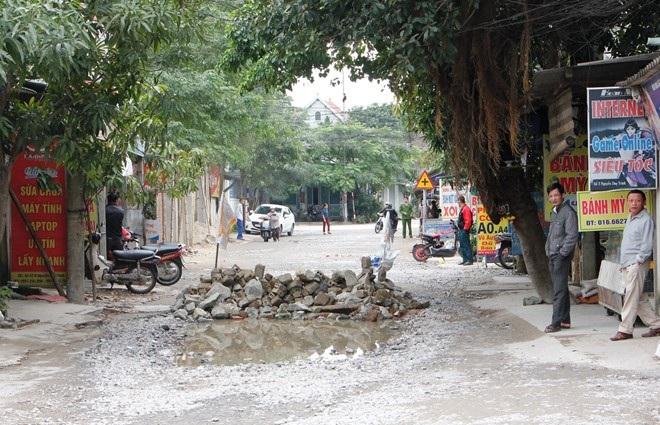 Người dân xếp gạch đá chặn các loại xe ôtô không cho lưu thông qua đường Nguyễn Duy Trinh. (Ảnh: Phạm Hòa)