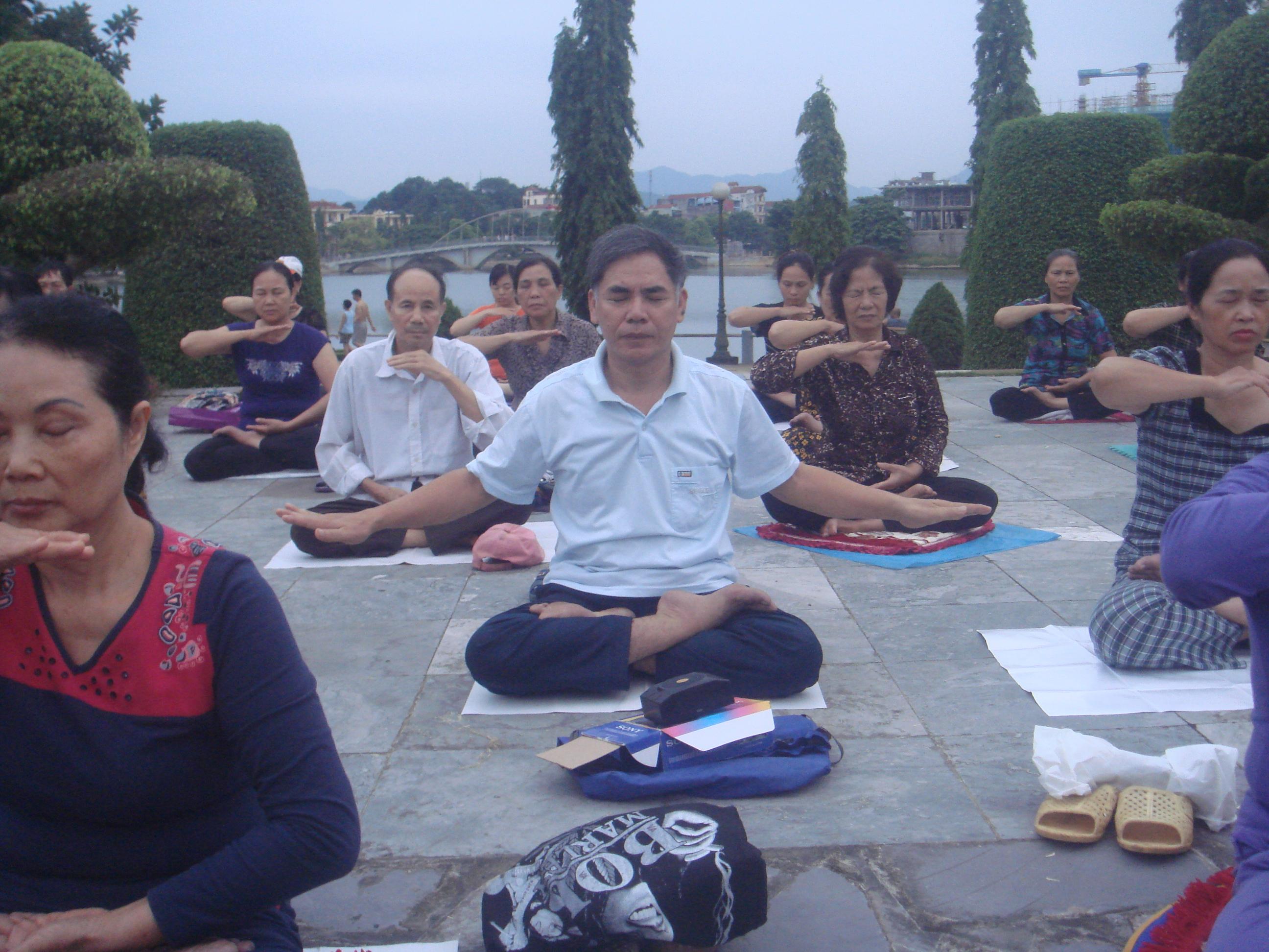 Anh Bái đang luyện bài Công pháp số 5 của Pháp Luân Công cùng mọi người ở công viên Yên Hòa thành phố Yên Bái (người áo trắng cộc tay ở giữa). Ảnh do anh Bái cung cấp.