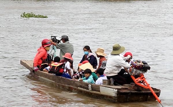 Mỗi ngày có hơn 1.200 học sinh người Việt ở vùng biên giới tỉnh Kandal (Campuchia) vượt sông trong mùa lũ về An Phú học tiếng Việt. (Ảnh: Cửu Long)