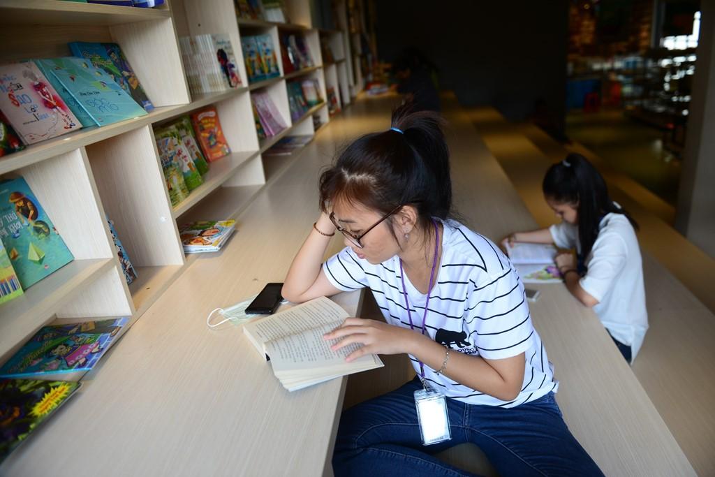 Những chiếc bàn lớn gắn liền với kệ sách để bạn đọc tiện lợi hơn khi chọn sách.