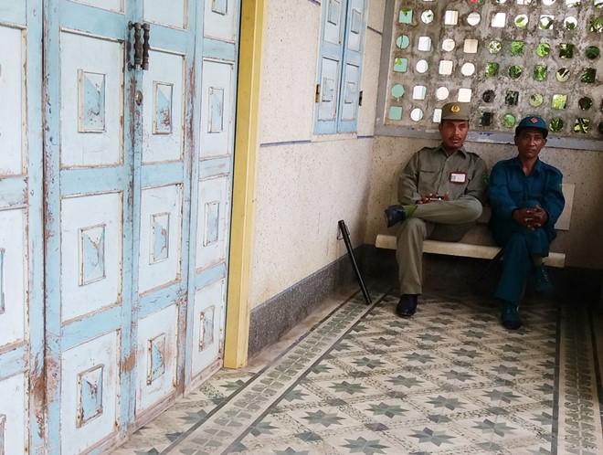 Hai bảo vệ dân phố và dân phòng túc trực trước cửa nhà ông Thái từ tối hôm trước đến sáng 19/10. Ảnh: Việt Tường.