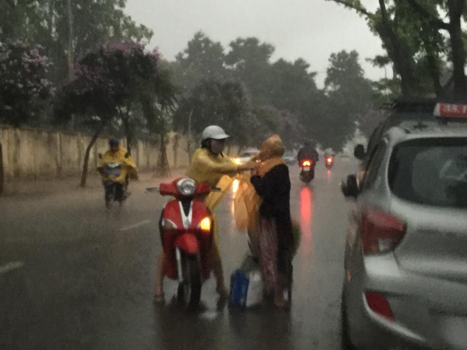 Cô gái dừng lại và tự tay mặc áo mưa cho bà cụ.