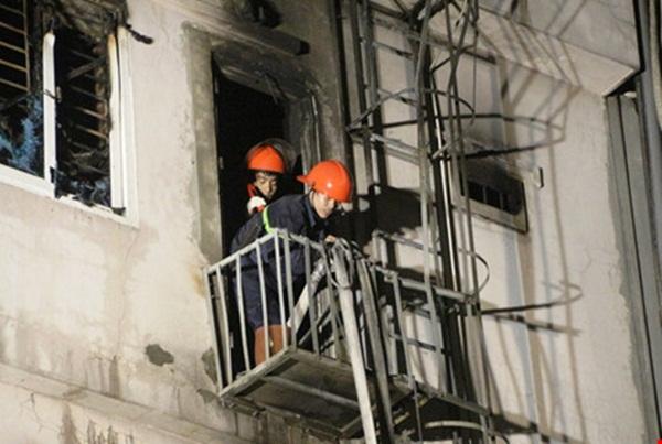 Hai lính cứu hỏa thả vòi dẫn nước xuống phía dưới trước khi rời khỏi hiện trường vụ cháy.