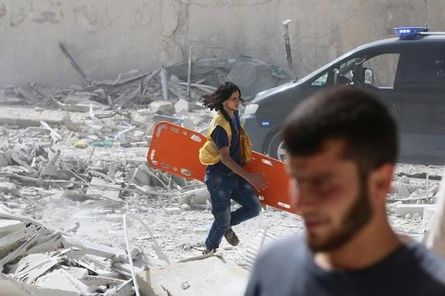 A man runs with a stretcher in a damaged site after airstrikes on the rebel held al-Qaterji neighbourhood of Aleppo