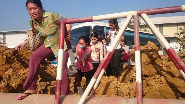 Công nhâncông ty trèo qua những đống đất vào làm việc.