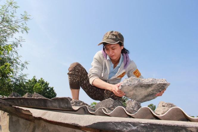 Minh Phương leo lên mái nhà, dùng đá, tấm tôn để che nắng, tránh mưa.