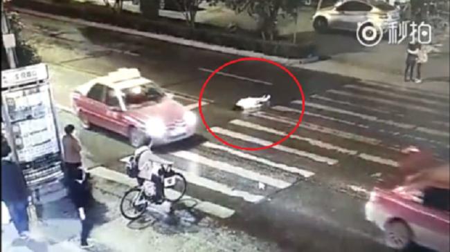 Trung Quốc: Cô gái bị xe cán 2 lần, đám đông thờ ơ bỏ mặc.1