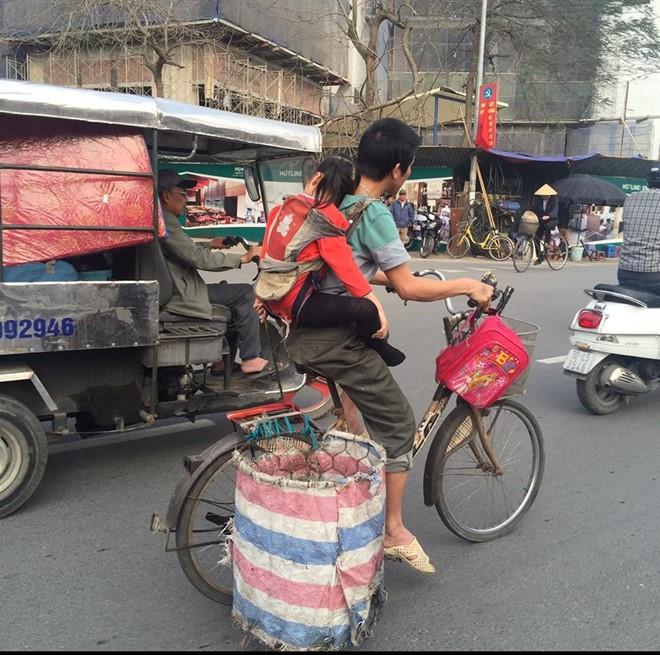 Bé gái gục đầu vào vai cha trên chiếc xe đạp đi nhặt rác.