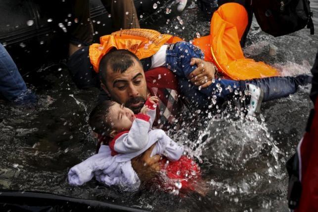 Một người nhập cư Syria đang ôm đứa con khi cố bơi vào bờ ở đảo Lesbos, Hy Lạp, sau khi vượt biển. Ảnh: Reuters