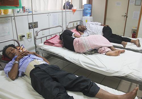 Sáng 29/5, ông Toán vẫn còn tê liệt, sưng tấy hai chi dưới. Ở giường cạnh bên là bố con ông Hồ Nghĩa đau nhức khắp cơ thể.