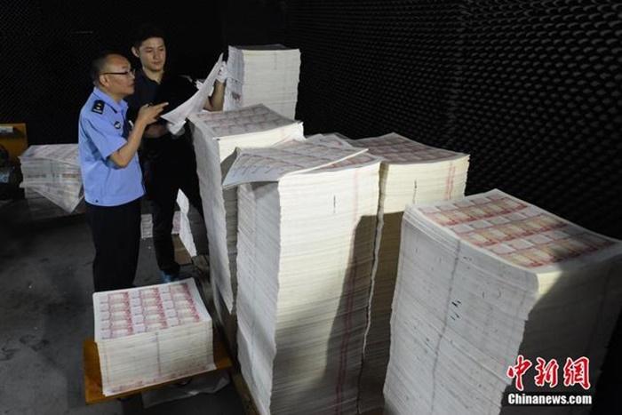 Cảnh sát bên số tiền giả đang được in ấn