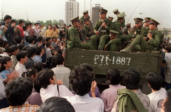 Những người biểu tình ủng hộ dân chủ bao quanh một chiếc xe tải chở binh sĩ Quân Giải phóng nhân dân trên đường đến Quảng trường Thiên An Môn ở Bắc Kinh vào ngày 20/5/1989. (Catherine Henriette / AFP / Getty Images)