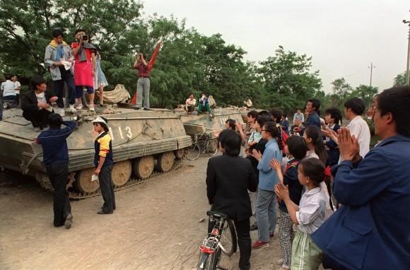 Những người biểu tình ủng hộ dân chủ hoan nghênh các sinh viên đến từ Đại học Bắc Kinh, đang đứng trên những chiếc xe tăng chở lính của PLA ở Bắc Kinh vào ngày 21/5/1989. Họ đang cố gắng thuyết phục những người lính không tuân theo tình trạng thiết quân luật đã được tuyên bố ngày hôm trước. (Catherine Henriette / AFP / Getty Images)