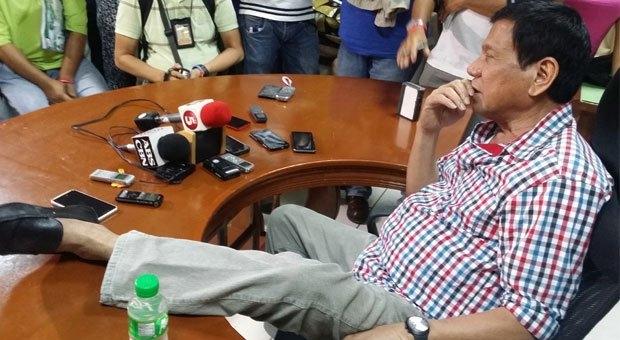Ông Duterte khoe đôi giày không nhãn hiệu của mình cho các phóng viên (ảnh: Inquirer)