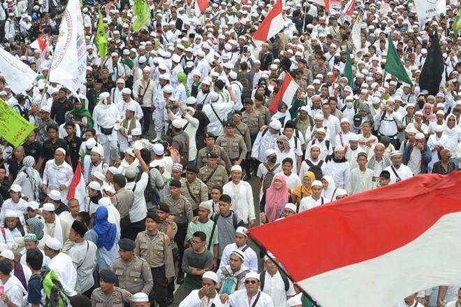 Cảnh sát Indonesia đứng thành hàng bảo vệ giữa đám đông của cuộc biểu tình. Ảnh: AFP