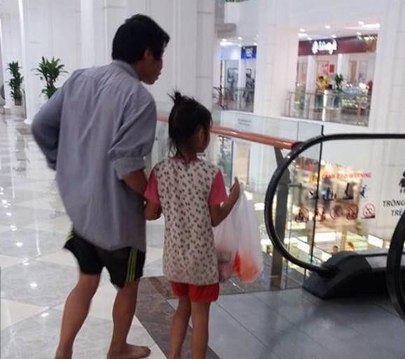 Người cha chân đất nắm taycon gái trong trung tâm thương mại.
