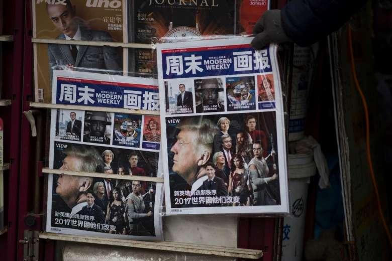 """Một tạp chí tiếng Trung ngày 14/12/2016 đăng trên trang bìa hình Tổng thống đắc cử Donald Trump ở một quầy báo Thượng Hải, với tiêu đề """"Những người anh hùng mới tạo nên những trật tự mới và vì họ thế giới thay đổi"""".(Ảnh: JOHANNES EISELE/AFP/Getty Images)"""