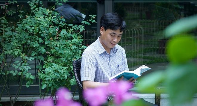 Anh Phùng Anh Việt đang đọc Chuyển Pháp Luân. (Ảnh: ĐKN)