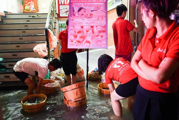 Những nhân viên một cơ sở massage cố gắng che chắn nước và vớt đồ đạc bị trôi ra ngoài.