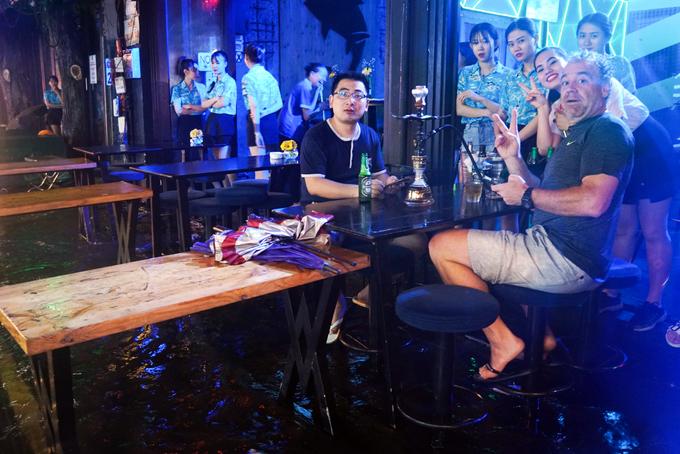 Cơn mưa lớn khiến không khí phố Tây không còn náo nhiệt như mọi ngày. Dù vậy nhiều quán ăn, quầy bar, cửa hàng... vẫn phục vụ du khách bất chấp thời tiết xấu.