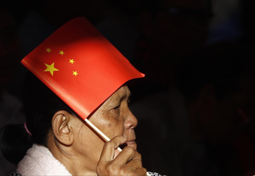 Một phụ nữ cầm cờ Trung Quốc tại một sự kiện ở Phnom Penh - Campuchia hồi tháng 7-2018.
