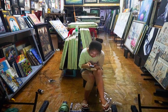 """""""Chưa bao giờ tôi thấy mưa mà từ sáng đến tối vẫn chưa ngớt, cứ tưởng Sài Gòn không bị ảnh hưởng của bão. Bình thường phố Tây mưa lớn nước cũng không tràn vào nhà nhiều như vậy đâu"""", chủ tiệm tranh cho biết."""